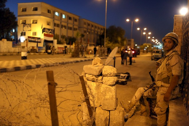 A soldier stands guard at the entrance of a school used as a voting centre on the first day of the second round of parliamentary elections, in Suez